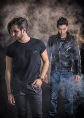 Two attractive young hard rock men posing in studio. Black background