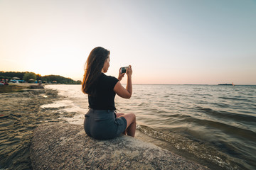 woman sits on a beach and takes picture of the seaside