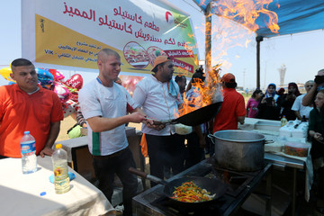 Palestinians prepare pizza with an Italian chef (not pictured) during a food and cultural exchange event at the seaport of Gaza City