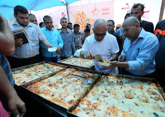 An Italian chef serves a piece of pizza to a Palestinian man during a food and cultural exchange event at the seaport of Gaza City