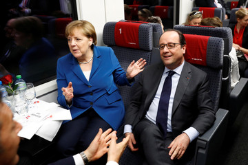 Italy's Prime Minister Matteo Renzi, Germany's Chancellor Angela Merkel and France's President Francois Hollande speak to one another while travelling through the Gotthard Rail Tunnel in Pollegio