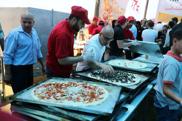An Italian chef prepares pizza for Palestinians during a food and cultural exchange event at the seaport of Gaza City