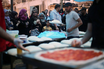 Palestinians watch the preparation of pizzas by an Italian chef during a food and cultural exchange event at the seaport of Gaza City