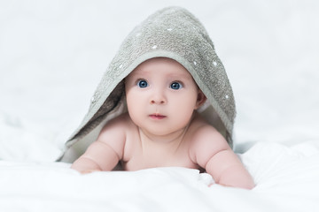 Cute baby girl or boy after shower with towel on head in white sunny bedroom. Child with big blue eyes relaxing in bed after bath