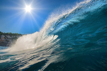 Surfing wave. Blue ocean crest. Sea water with sun over blue sky on backround. Nobody on image