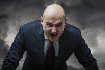 Angry boss. Businessman in suit with very angry face screaming.