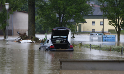 A car stands in the water in the flooded street in the Bavarian village of Triftern