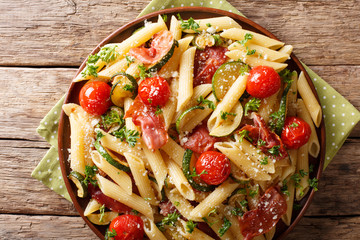 Delicious hot penne pasta with ham, cherry tomatoes, zucchini and cheese close-up. Horizontal top view