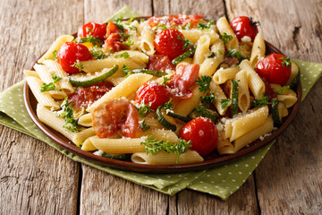 Tasty penne pasta with fried ham, tomatoes, zucchini and Parmesan cheese close-up. horizontal