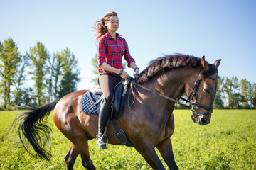 Happy young woman galloping horseback on field and enjoying feeling of freedom