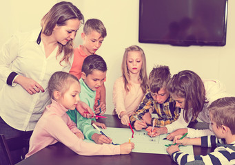 Children with teacher drawing together in classroom