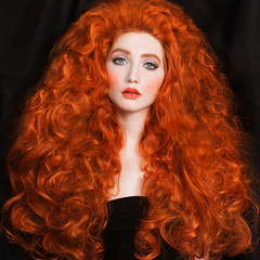 Redhead woman with very long curly hair with unusual appearance in a black dress on a black background. Lovely girl with pale skin with a bright appearance. Blue eyes and pink lips. Spectacular makeup