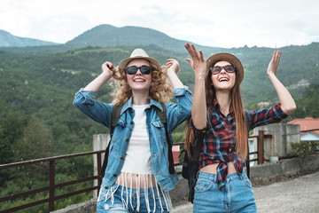 Two girls in hats traveling through ruins ander rain