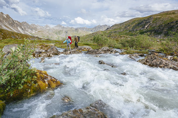 A Man And Woman Crossing A River In Talkeetna Range In Alaska, Usa