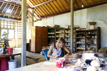 Young woman in ceramic workshop.