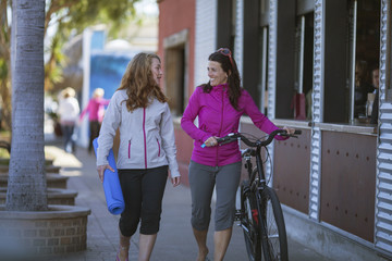 A mother and teenage daughter walking to yoga class together.