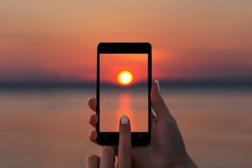 Mobile phone in a woman's hand takes pictures of the sunset