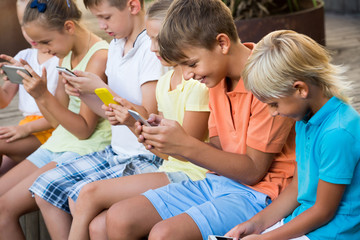 children in school age looking at mobile phones and sitting outdoors