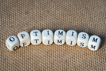 optimism word made from toy cubes with letters