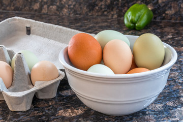 Horizontal photo of multicolored eggs in a white bowl and some still in the grey carton to the side on a kitchen counter with a green pepper in the background