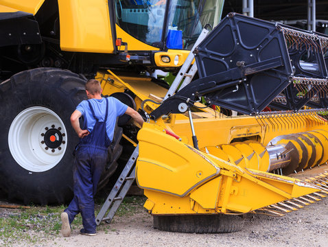 The mechanics repair the yellow Combine harvester in the farm yard. Concept theme repair, mechanics, production, industry, agribusiness company, production of food and agricultural production.