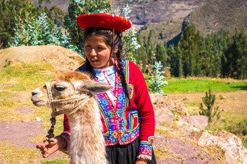 Native Peruvian girl with her lama animal in Sacred Valley, Cusco, Peru