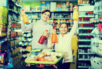Woman customer with girl looking for refreshing beverages