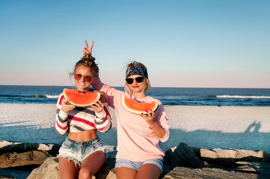 Happy girls eating watermelon on the beach. Friendship, happiness, beach, summer concept.