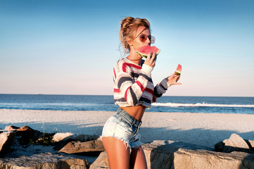 Happy woman eating watermelon on the beach.