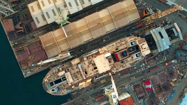 Aerial top down view of unfinished ship at the shipyard