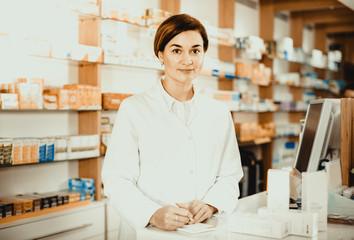 Female pharmacist offering help in choosing at counter in pharmacy