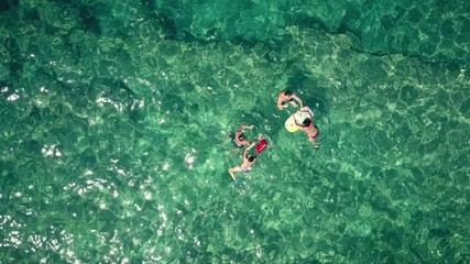 Aerial top down view of a adult couples bathing in the sea