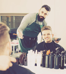 male hairdresser showing resulting haircut to client at hair salon