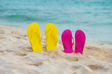 Yellow and pink sandals stand in the sand against the background of the sea.