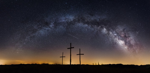 the milkyway galaxy arching over three crosses