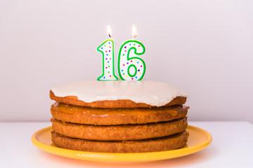 Sixteenth birthday candles on rustic layered vegan vanilla cake