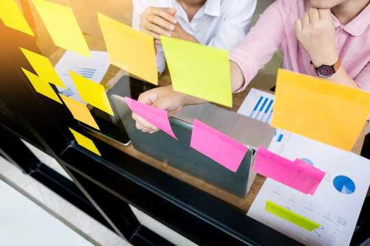 business man sticking adhesive notes on glass wall in office and discussting with team