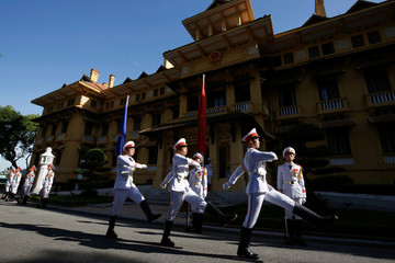 Honour guards march past the ASEAN flag and Vietnamese flag in the background, after a flag raising ceremony to mark the 50th anniversary of the regional group at Vietnam's Ministry of Foreign Affairs in Hanoi