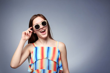 Young emotional girl wearing sunglasses, on grey background