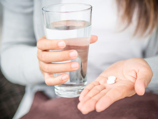 Closeup woman hand with pills medicine tablets and glass of water for headache treatment. Healthcare, medical supplements concept