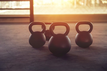 Sport equipment in gym. Kettlebell on floor background with sunlight effect. Fitness training.