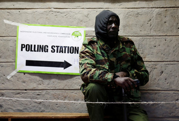 A security policeman stands outside a polling station during the presidential election in Kibera