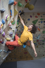 Rock climber bouldering intdoors on climbing wall