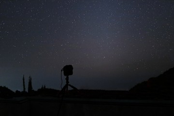 Silhouette camera on tripod with beautiful stars on night sky background.