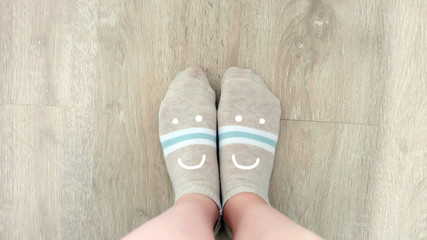 Selfie Female Legs Wear Brown Socks on a Wooden Floor Background Great For Any Use.