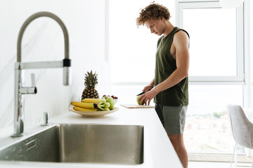 Concentrated man standing at the kitchen and cooking