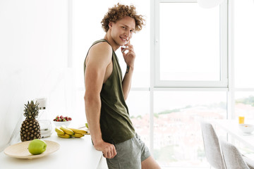 Cheerful man standing at the kitchen and talking by phone