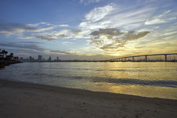 sand and palm trees line the shore of Coronado Island as the sun slowly rises above the Coronado Bridge