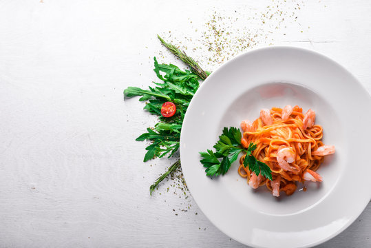 Pasta with shrimp and tomato sauce. Italian traditional food. On a wooden background. Top view. Free space for your text.