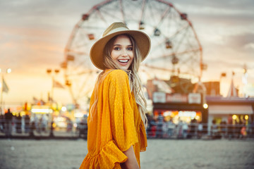 Papiers peints Attraction parc Beautiful exited smiling tourist woman having fun at amusement park at hot summer day trip on the beach.